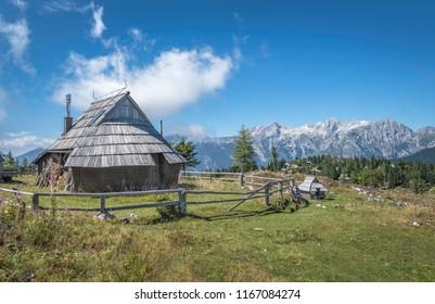 Traditional wooden cottage on Velika planina (Big Pasture Plateau) with panoramic view of Kamnik-Savinja Alps, Slovenia