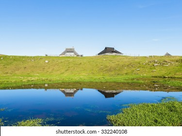 Traditional wooden cottages on green field on Slovenian alps and their reflections in water, Velika Planina, Kamnik, Sovenia, Europe