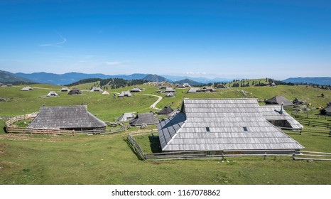 Traditional wooden cottages in village on Velika planina (Big Pasture Plateau) with pastures, Slovenia