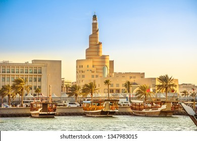 Traditional wooden dhow anchored at Dhow Harbor in Doha Bay with spiral mosque and minaret in the background at sunset. View from Corniche promenade. Qatar, Middle East, Arabian Gulf.
