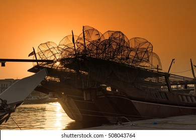 A traditional wooden dhow boat at sunset loaded with empty lobster pots ready to go out to sea for a fishing trip with a golden orange sunset background
