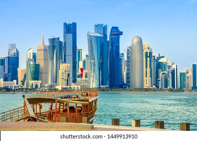 Traditional wooden dhow on foreground at Doha Bay and skyscrapers towers of West Bay skyline on background. Capital of Qatar, Middle East, Persian Gulf. Sunny blue sky. Urban modern cityscape.