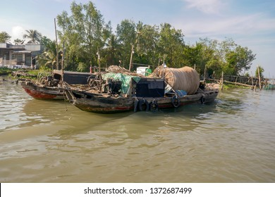 Traditional wooden dragon boats with fishing nets on waterfront of Mekong River Delta in rural Vietnam.