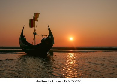 Traditional wooden fishing boat known as moon boat on beach near Cox's Bazar in southern Bangladesh at sunset