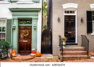 Traditional Wooden Front Doors of Old Coloured Brick Buildings with Halloween Decorations