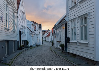 Traditional wooden houses in Gamle Stavanger. Gamle Stavanger is a historic area of the city of Stavanger in Rogaland, Norway. Beautiful summer sunset with coloured sky. July 2019