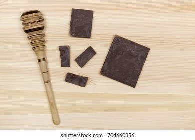Traditional wooden Molinillo whisk of Mexico and pieces of mexican chocolate bar on wooden background.