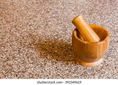 A traditional wooden mortar and pestle on a granite kitchen worktop