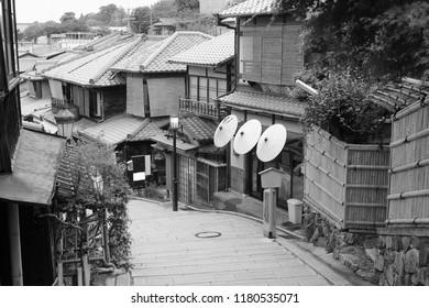 Traditional wooden neighborhood buildings and Japanese parasols in Sannen Zaka (Sannenzaka) street, Higashiyama district, Kyoto, Japan