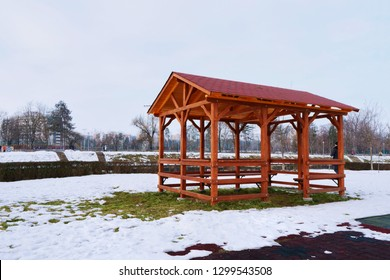 Traditional wooden pavilion on the river banks in the snow covered landscape in winter