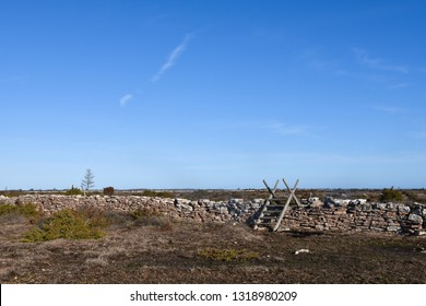 Traditional wooden stile by a stone wall in a great plain grassland at the swedish island Oland