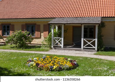 Traditional wooden vintage house yard with blooming greenery. Northern European style.
