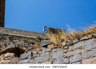 Traditional Worker Making Repairs on the Ancient Stone Walls at Golconda Fort in Hyderabad, India