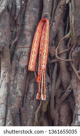 Traditional woven Slavic belt on the background of nature, gray trunks of old trees, old window shutters on the railing of the ancient entrances.
