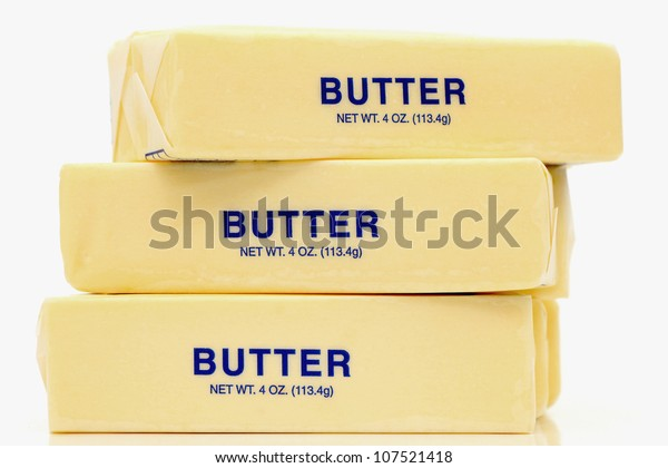 Traditional wrapped butter sticks on white background