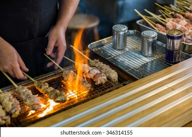Traditional yakitori chicken stand in Japan at street food vendor market, grilled satay. Japanese Food.
