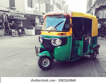 Traditional yellow green tuk tuk taxi on the street. Indian public transport on the streets of new Delhi. Tricycle vintage retro motorcycle 50-60 years of the 20th century