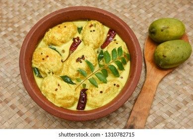Traditional yellow mango curry or Mampazha Pulissery sweet and sour dish Kerala India . Made from organic raw green mango, coconut milk, seasoned with curry leaves, mustard, Indian red Kashmir chilli.