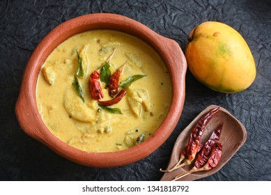 Traditional yellow mango curry or Mampazha Pulissery sweet and sour dish Kerala India . Made from organic raw ripe mango, coconut milk, seasoned with curry leaves, mustard, Indian red Kashmir chilli.