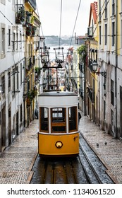 Traditional yellow tram in a narrow street in Lisbon on a rainy Winter day, with the river Tagus defocused in the background.