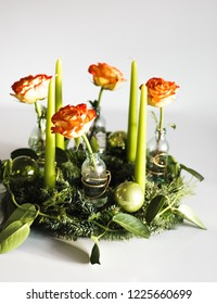Traditional yet modern German Advent wreath, a round circle with evergreen and fir branches, four candles and festive holiday or christmas decoration such as baubles or glass ornaments