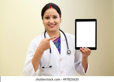 Traditional young female doctor holding tablet computer
