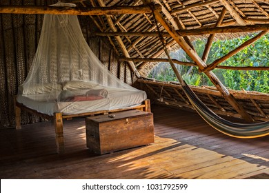 Traditional Zanzibar style open air hostel with wooden furniture, hammock and mosquito net. Cozy wooden interior of Zanzibar hostel.