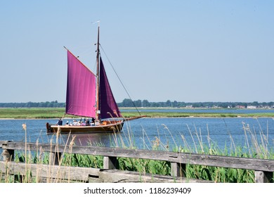 Traditional Zeesboot fishing boat with purple sails in Zingst, Germany