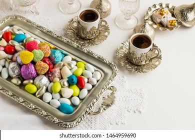 Traditional,Colorful Turkish Candies on the handmade table lace cloth with two cup of coffee.Stylish silver coffee set,conceptual image for celebrations.
