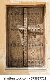 A traditionally carved Arabian door in the adobe wall of a restored building. Strong sunlight throws shadows over the carvings, door handles and door nails.