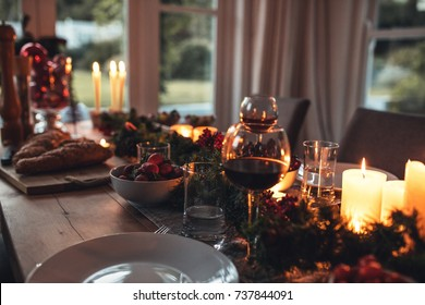 Traditionally decorated christmas table. Christmas dishware on the wooden dining table at home.