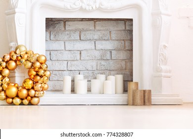 Traditionally decorated for Christmas is a white fireplace.gold Christmas wreath near light candles on a floor