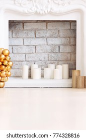 Traditionally decorated for Christmas is a white fireplace.gold Christmas wreath near light candles on a floor. Place for text