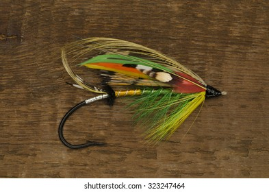 Traditionally dressed Green Highlander salmon fly shot against a wooden background