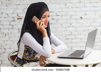 Traditionally dressed Muslim Woman working on computer and speaking on telephone on white brick wall.