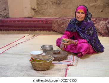 Traditionally dressed old Omani woman making sandalwood oil. Nizwa, Oman - 14/OCT/2016