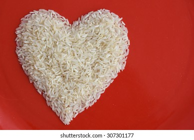 Traditionally Indian basmati Rice in heart shape in a red plate, isolated over white with copy space.Symbol of love or LUV. White rice or biriyani rice Kerala India