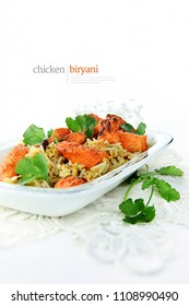 Traditionally prepared and cooked Indian chicken biryani with coriander garnish and pillau rice. Shot against a white background with generous accommodation for copy space.