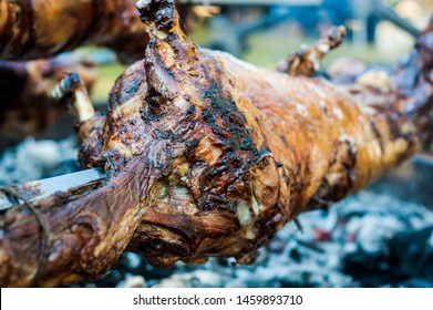 Traditionally suckling pig on a rotating spit with fire and smoke