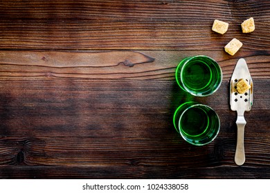 Traditions of drinking absinthe. Special spoon and sugar cubes near shots on dark wooden background top view copy space