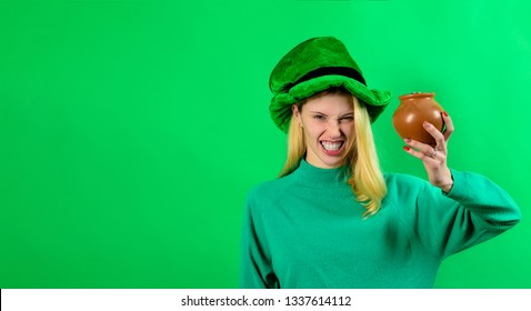 Traditions of Saint Patrick Day. St. Patrick's day celebrations. Angry girl in Leprechaun hat holds pot of gold. Coin. Woman holds pot of gold. Female in green costume and leprechaun top hat. 17 March