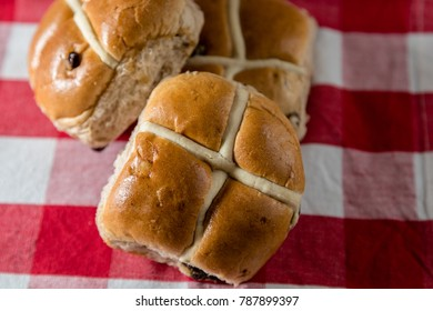 Traditonal Easter hot cross buns on a red and white checked cloth