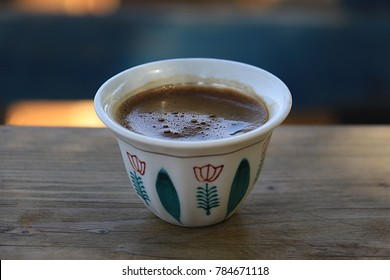 A traditonal Lebanese coffee cup on wooden pane.