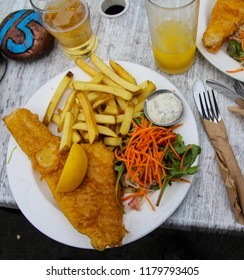 Tradittional Brittish Fish and Chips lunch served with fresh salad and tartar sauce at a restaurant in the UK