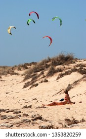 TRAFALGAR, SPAIN - SEPTEMBER 14, 2008 - Tourist relaxing on the beach with kitesurfers to the rear, Cabo Trafalgar, Cadiz Province, Andalusia, Spain, Europe, September 14, 2008.