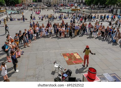 Trafalgar Square, London, UK -  July 21, 2017: Street performer with large crowd watching.  Taken from the National Portrait Gallery, looking down.