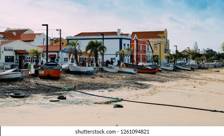 Trafaria, Portugal - Dec 16, 2018: Restaurants and bars along the seafront with wooden boats and pollutio at Trafaria, Portugal