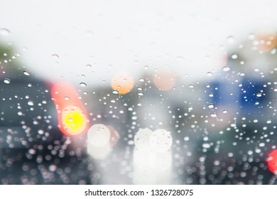 Traffic abstract in rain. Traffic seen from  inside a car. Rain drops on windshield and car tail lights in bokeh.