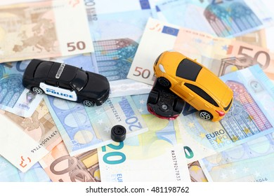 traffic accident of two toy cars and a police car helping in a european banknote background