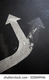 traffic arrow signage on an asphalt road indicating a detour